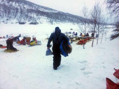 Dag Torulf bærer med seg utstyr ned til hundene. Straks er det avgang. Foto: Birger Altmann