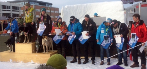 Her står en stolt hundekjører i blå jakke etter å ha gjort en knalløp.  F.v. Birgitte Næss Wærner, Sigrid Ekran, Ronny Frydenlund, Harald Tunheim, Dag Torulf Olsen, Alf-Einar Hernes, Nina Skramstad.