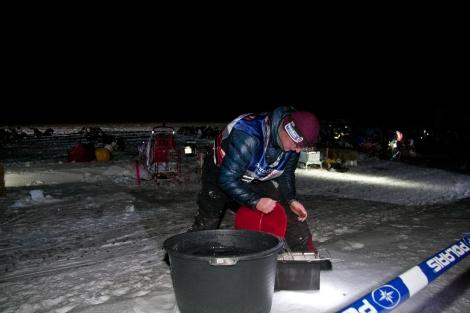 Dag Torulf henter vann som han skal varme opp og blande hundeforet i. Slik får hundene i seg både mat og væske. Foto: Eirik Palm